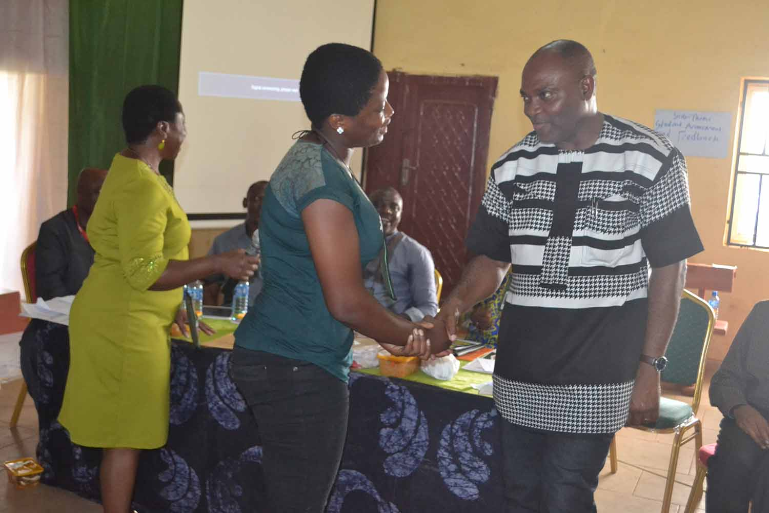 Winners of the Poetry workshop prizes in a hand shake with the Vice Chancellor