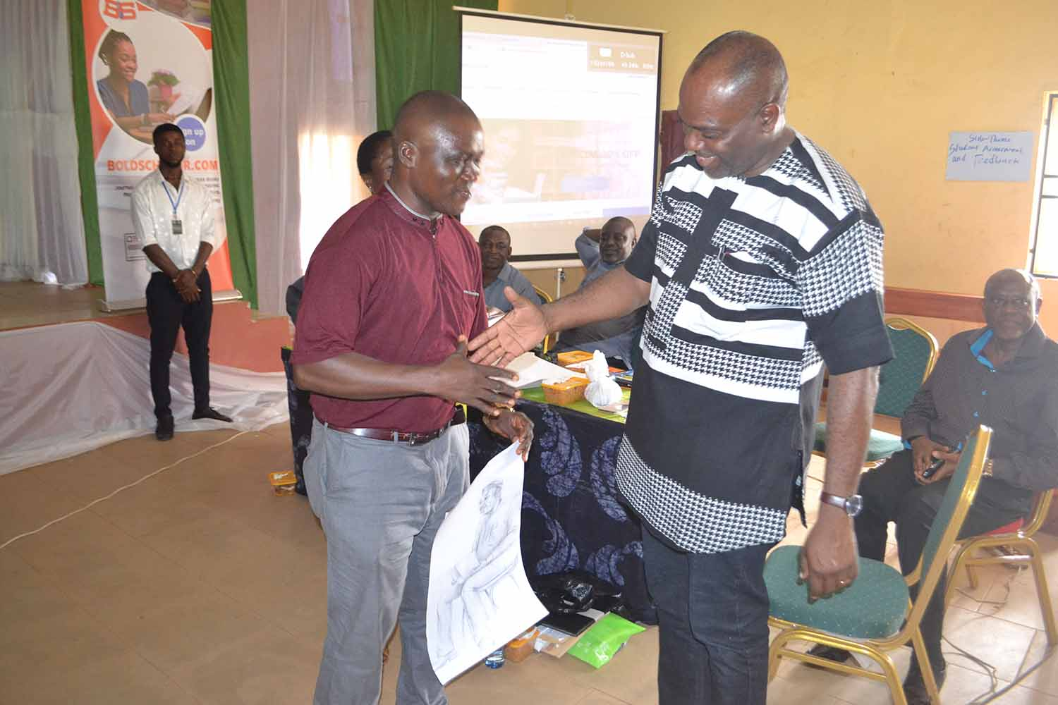 First Prize winner in the Drawing workshop, Mr Ukie Ogbpnna, in a handshake with the VC
